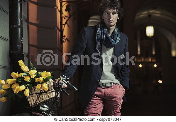 Young stylish guy next to bicycle - csp7073047