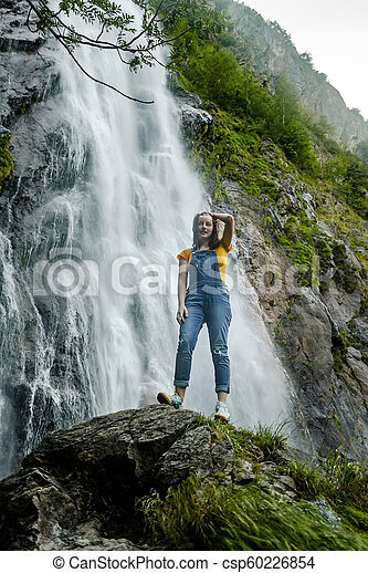 Young teenage girl standing on the big stone near waterfall - csp60226854