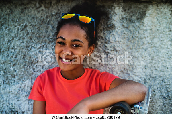 Young teenager girl sitting outdoors in city, leaning on concrete wall. - csp85280179