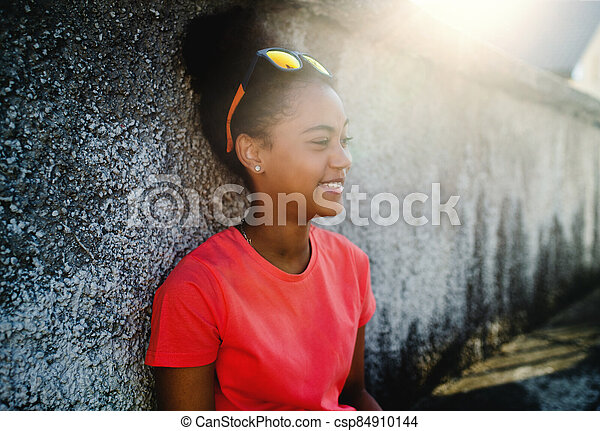 Young teenager girl sitting outdoors in city, leaning on concrete wall. - csp84910144
