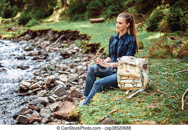 Young tourist woman sitting on the shore of a mountain river and looking at a beautiful landscape. Hiking woman with backpack relaxing - csp38520688