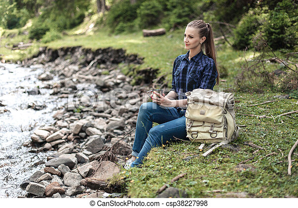 Young tourist woman sitting on the shore of a mountain river and looking at a beautiful landscape. Hiking woman with backpack relaxing - csp38227998