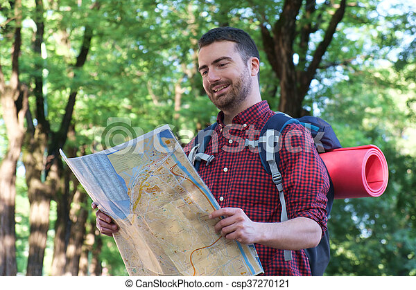 young urban traveler consulting a map to find the right path - csp37270121