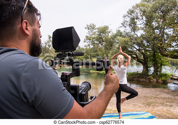 young videographer recording while woman doing yoga exercise - csp62776574