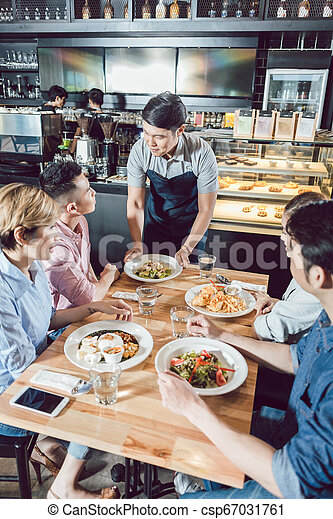 Young waiter serving food in the restaurant - csp67031761