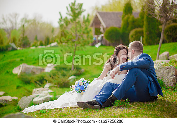 Young wedding couple enjoying romantic moments outside on a summer meadow - csp37258286