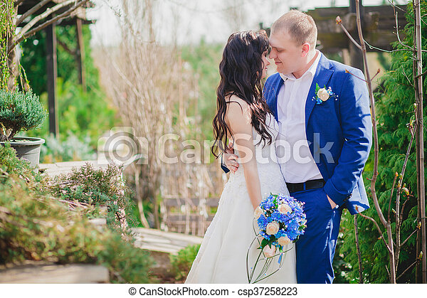 Young wedding couple enjoying romantic moments outside on a summer meadow - csp37258223