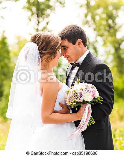 Young wedding couple enjoying romantic moments outside on a summer meadow - csp35198606