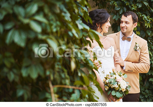 Young wedding couple enjoying romantic moments outside - csp35807505