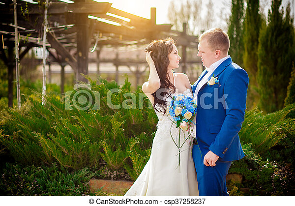 Young wedding couple enjoying romantic moments outside on a summer meadow - csp37258237