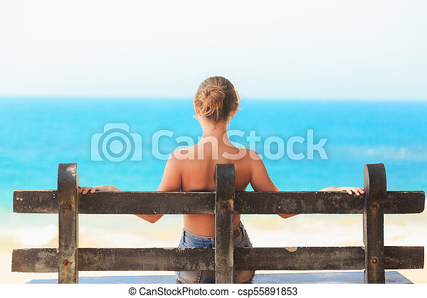 young white girl sitting alone on a wooden bench in summer young