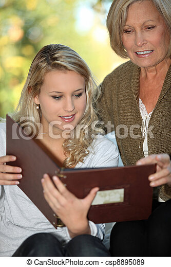 Young woman and her grandmother looking at a photo album - csp8895089