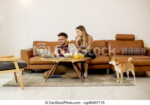 Young woman and young man using laptop for onlin payment while sitting by sofa with their shiba inu dog at home - csp90407115