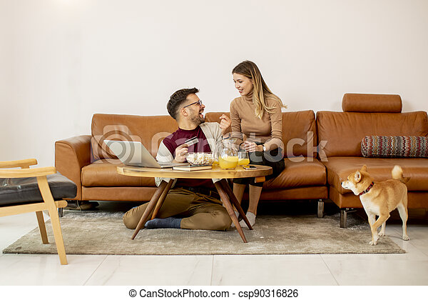 Young woman and young man using laptop for onlin payment while sitting by sofa with their shiba inu dog at home - csp90316826