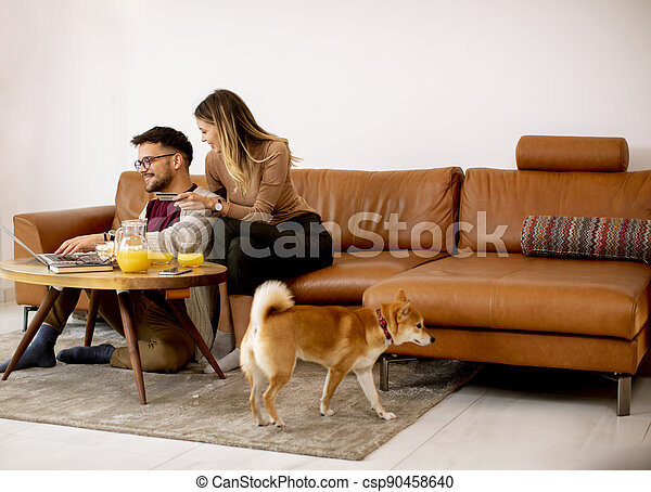 Young woman and young man using laptop for onlin payment while sitting by sofa with their shiba inu dog at home - csp90458640