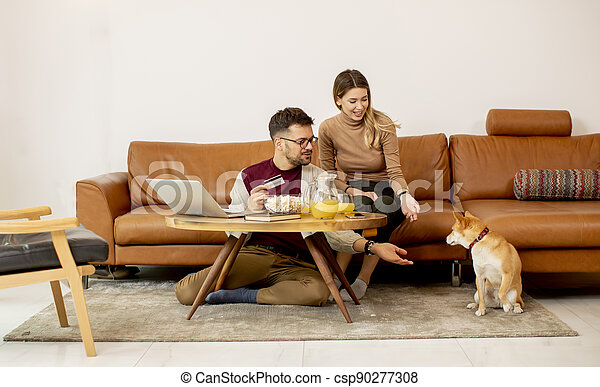 Young woman and young man using laptop for onlin payment while sitting by sofa with their shiba inu dog at home - csp90277308