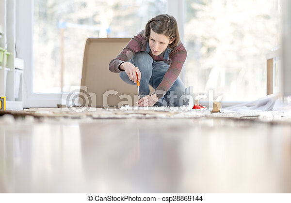 Young Woman assembling a DIY furniture at home kneeling on the floor in front of a bright glass window  - csp28869144