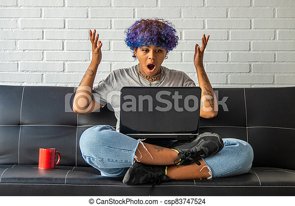 young woman at home with laptop sitting on the living room sofa - csp83747524