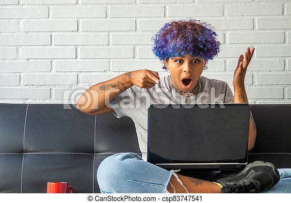 young woman at home with laptop sitting on the living room sofa - csp83747541