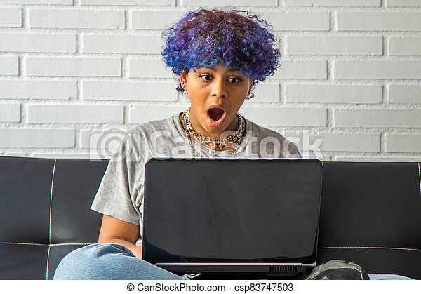 young woman at home with laptop sitting on the living room sofa - csp83747503