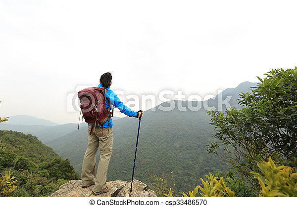 young woman backpacker hiking on mountain peak - csp33486570