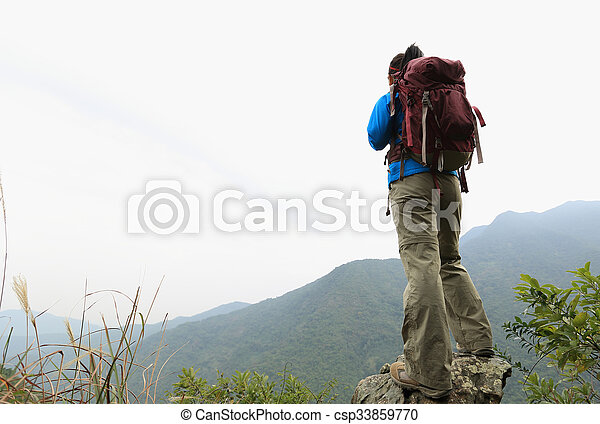 young woman backpacker hiking on mountain peak - csp33859770