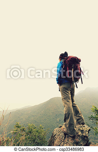 young woman backpacker hiking on mountain peak - csp33486983