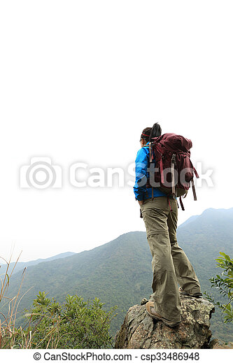young woman backpacker hiking on mountain peak - csp33486948