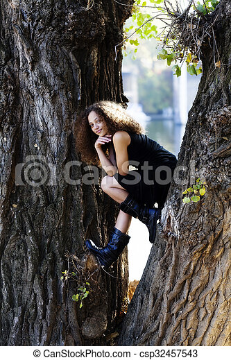 Young Woman Black Dress Sitting Between Tree Trunks - csp32457543