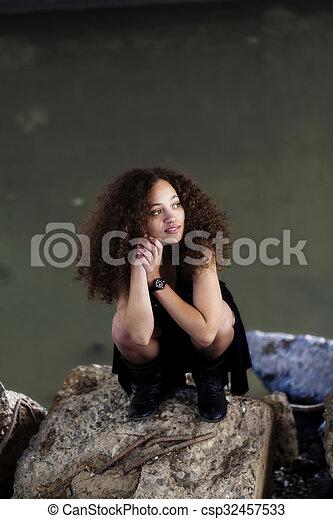 Young Woman Black Dress Squatting On Concrete Blocks - csp32457533