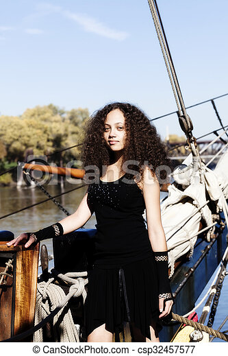 Young Woman Black Dress Standing On Bow Sailing Ship - csp32457577