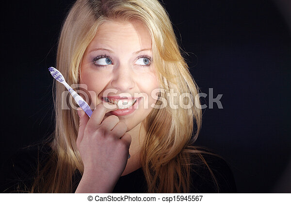 young woman brushing teeth - csp15945567