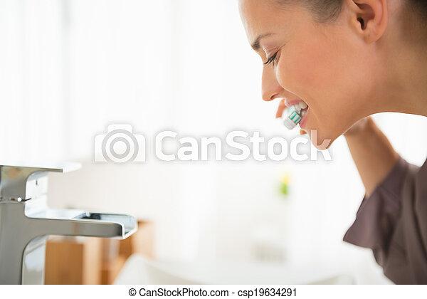 Young woman brushing teeth - csp19634291