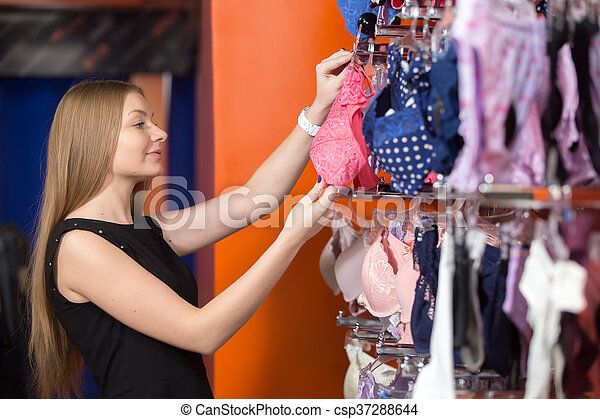 7300018b8 Young woman buying underwear. Portrait of smiling young beautiful ...