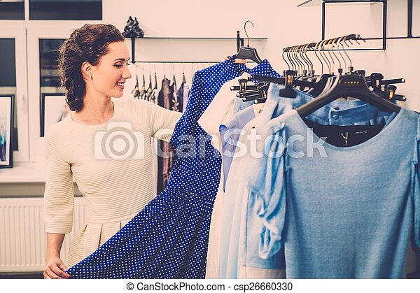 Young woman choosing clothes on a rack in a showroom  - csp26660330
