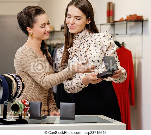 Young woman choosing jewellery with shop assistant  help - csp23716646