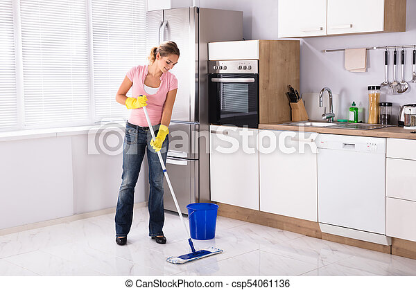 Smiling young woman cleaning kitchen floor with mop in kitchen at home.