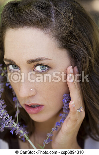Young woman closeup portrait outdoors with floweres - csp6894310