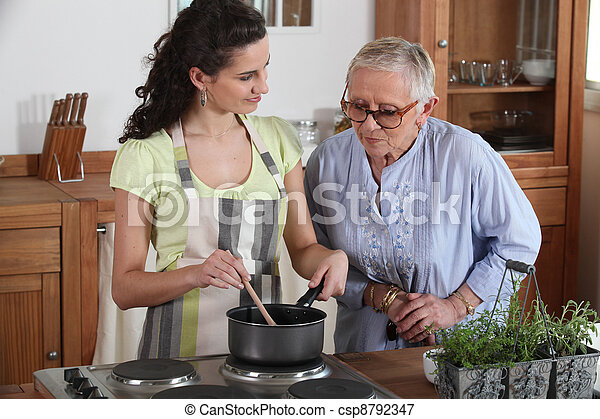 Young woman cooking for an elderly lady - csp8792347