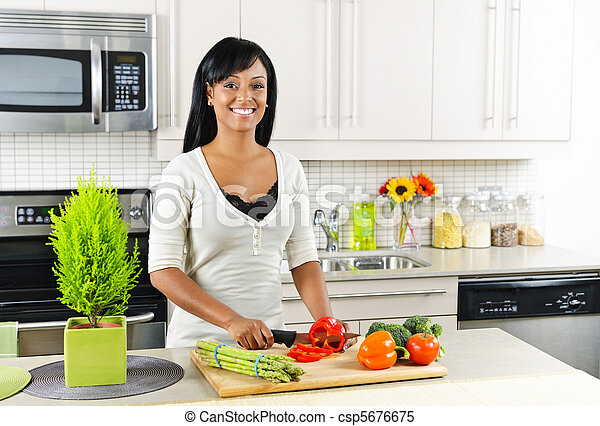 Young woman cutting vegetables in kitchen - csp5676675