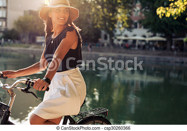 Young woman cycling by a pond - csp30260366