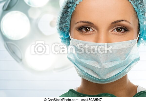 Young woman doctor in cap and face mask in surgery room interior - csp18928547
