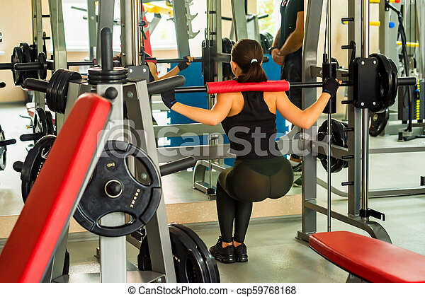 young woman does squats in smith machine in gym back view