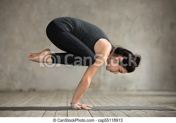 young woman doing bakasana exercise young woman