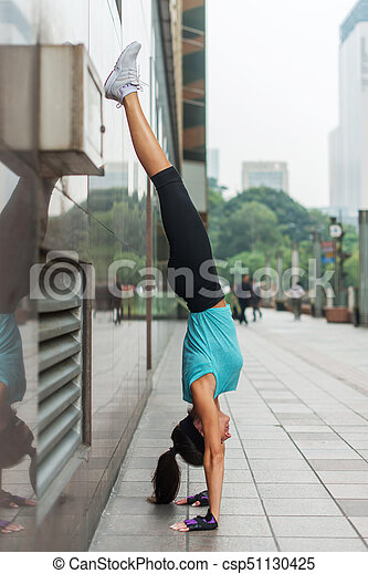 young woman doing handstand exercise against the wall on