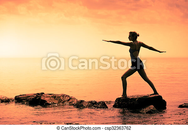 Young Woman doing the Warrior Yoga Position in Front of the Ocean - csp32363762