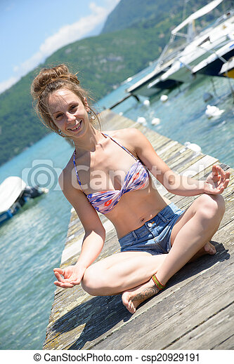 young woman doing yoga on the waterside - csp20929191