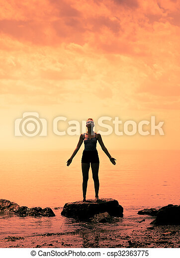 Young Woman doing Yoga Position in Front of the Ocean - csp32363775