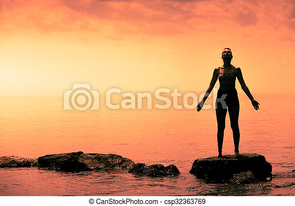 Young Woman doing Yoga Position in Front of the Ocean - csp32363769