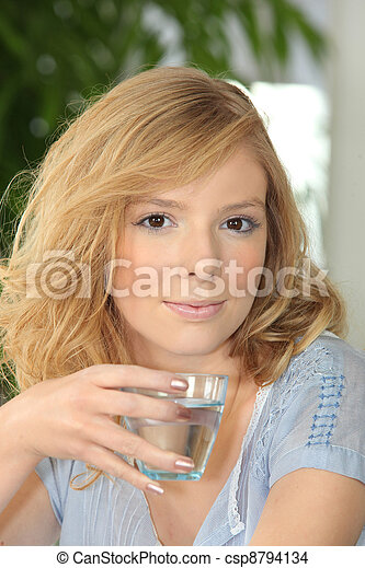 Young woman drinking a glass of water - csp8794134